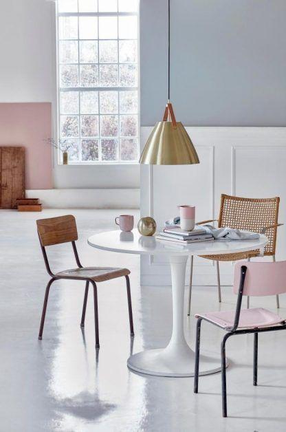 złota lampa wisząca nad stołem w salonie z różowymi ozdobami