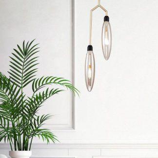Złota lampa ze szklanymi kloszami nad komodą