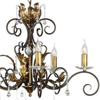 złoto brązowy żyrandol ze świecznikami i kryształowymi kroplami