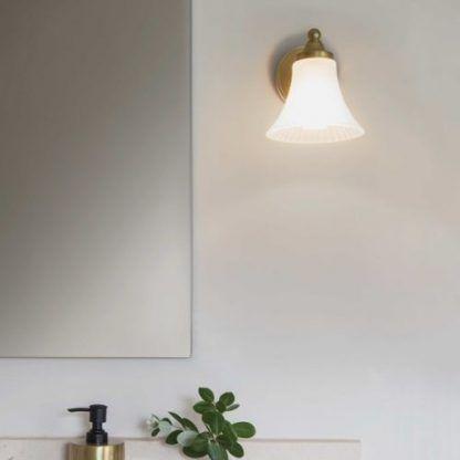 złoty kinkiet z szklanym kloszem do łazienki obok lustra