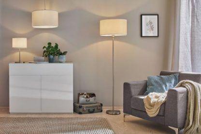 Lampa podłogowa Tessa przy fotelu w salonie